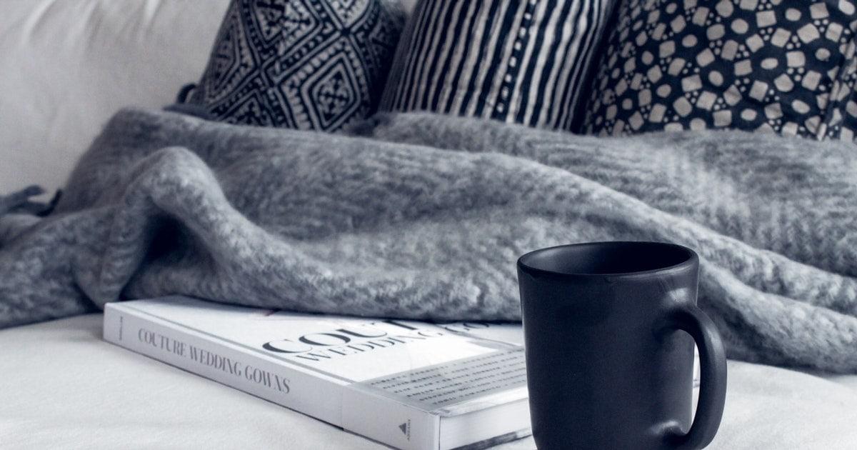Black Ceramic Mug On Round White And Beige Coaster On White 1421177